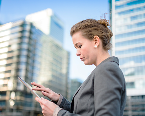 Business woman in city using iPad